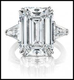 10 carat diamond engagement ring with trap-cut diamond shoulders, centering a 10.54 carat, D color, VVS2 clarity rectangular cut stone. Via Diamonds in the Library.