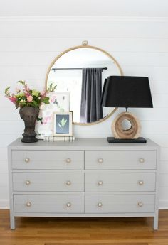 Simple styling over a bedroom dresser - large round mirror, lamp, and planter with two pieces of layered art