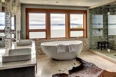 Contemporary lake view bathroom with freestanding tub and glass tile shower