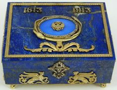 [DETAIL1] RUSSIAN SILVER & LAPIS JEWELED ENAMELED BOX by FABERGE - Dated 1913 on top. Has guilloche blue enamel design to top embellished with a double headed eagle crest design and encircled by a figural snake frame. Clad Griffin design to front. Dragon design to sides with jeweled handles and cabochon sapphire set. Has diamond set latch. Set on 4 scrolled feet. Faberge, 84 silver purity and town marks to bottom. Hold the Anders Juhaninpoika workmaster marks (Finnish, 1858-1933).