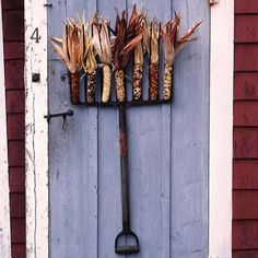 Farm-Inspired  For a country look, wedges ears of Indian corn between the tines of an old metal rake, using hot-glue to secure if necessary. Hang the finished rake on your door as an alternative to a traditional fall wreath.