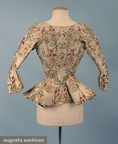 """Late 18th century silk brocade bodice. Horizontally ribbed silk brocaded w/ red, pink, yellow, green, gold, & silver in floral pattern, deep peplum, 2 small pocket flaps, 2 self covered back buttons, linen & silk linings, inside eyelets for lacing stomacher, B 22"""", W 18"""", L 23"""", Slv L 13.5"""""""