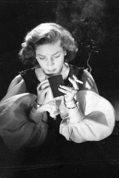 Lauren Bacall checking her make-up during a photo shoot, 1951