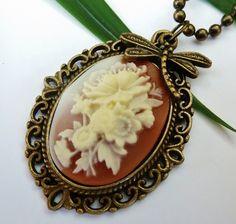 Halskette aus antikgoldfarbenem Metall mit schöner Gemme in braun-creme mit Rosenstrauß. Der kleine Libellen-Anhänger besteht aus Messing. Wenn I...