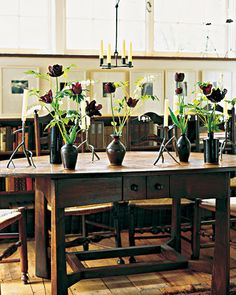 She+combined+'Black+Parrot'+tulips+and+white+bleeding+hearts+in+black+vases,+and+displayed+them+on+a+table+of+her+own+design.+The+vases+are+interspersed+with+twig-inspired+bronze+candlesticks+by+Pennsylvania+artist+Edward+Henderson.