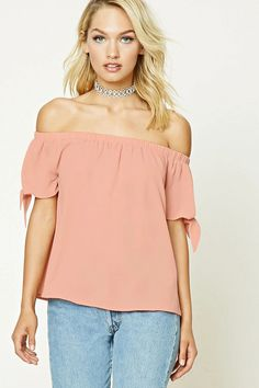 A crinkled woven top featuring an elasticized off-the-shoulder neckline, short sleeves, and a rounded hem.