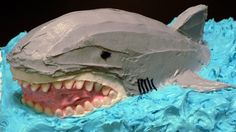 Snaggly-toothed shark cake !      For the shark, I decided to make two separate cakes: a white cake for the ocean, a red velvet cake for the shark's body. That way, when you cut into the shark, it would look like blood. And if there's anything a four-year-old boy wants to see, it's blood.