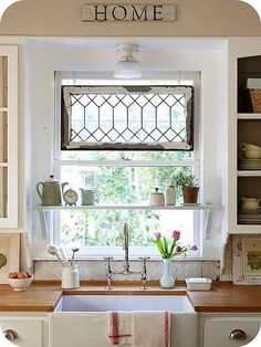 no cabinet doors,old tin back splash,old window hanging, wood counter tops, shelf, pulls, farm house sink