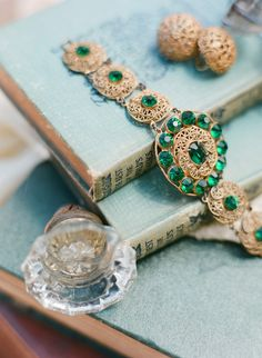 old world charm, emerald bracelet, gold clip on earrings, dusty books, and, door knobs