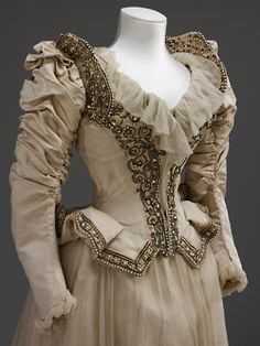 c. 1890    V: Heavy cream corded silk wedding dress and trained skirt, bodice with accentuated waist and dramatically flared peplum, shirred leg o'mutton sleeves. Embroidered with pearls, pastes and gathered silk lisse (crêpe chiffon). Shoes of white satin embroidered with bronze and crystal, silk stockings.