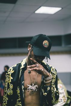 Travis Scott wearing  Versace Baroque Motif Silk Shirt, Off-Brand Travis Scott Madness Tour Cap, Nick Bhindi Custom Horse Pendant Chain
