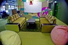 A comfortable and colorful living room serves as an unofficial meeting spot for employees and even features a drawing board.