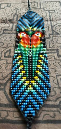 On this beautiful bracelet we see two guacamayos (macaws). The spirit of the Guacamayo symbolizes communication, flight, beauty, guidance in wisdom, color healing, self-confident and active. Guacamayos are the symbol of creative intelligence, inspiration, and freedom. These sacred bead work necklaces and bracelets are handmade by women from an indigenous cooperative from the Kamentsá tribe of the Sibundoy valley in southern Colombia. Each design is inspired by the visions received during…