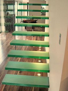 Glass cantilever staircase with full height independent glass panel balustrade and wall mounted handrail.