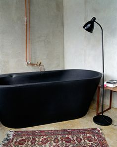 Sexy black soaker tub, concrete walls? exposed copper pipes in bathroom.