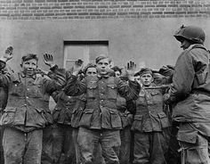 1945 A group of young German soldiers frightfully raise their hands at the business end of a paratroopers grease gun.