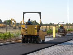 A rubber-tire roller follows the vibratory roller and helps fine-tune the compaction of the new asphalt mat, which is an essential step in the paving process. This is at a warehouse complex in West Sacramento, Calif.