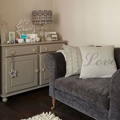 his cosy corner of the living room has a small love seat and painted cupboard in a neutral shade.