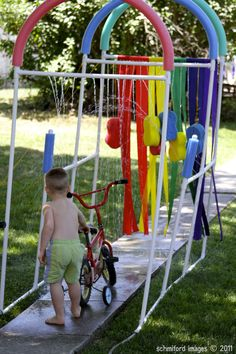 """I think we need this in our yard this summer! What a fun DIY sprinkler """"carwash"""" for the  kids. Made with PVC pipes and pool noodles - it's genius!   -Colleen at WrapsodyBaby.com"""