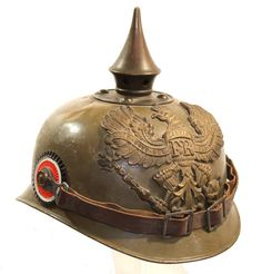 This WWI Prussian Field-Gray Ersatz Steel Pickelhaube realized $1375. in Auction IV. Register to bid in our next auction at grenadierauctions.com.