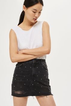 Add an edgy twist to your look with this denim mini skirt featuring a raw hem and rip and stud detail.