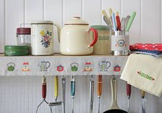 in the kitchen - I like everything in this pic- cans, teapot, embroidery, kitchen towel....