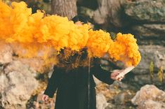Woman in a black coat with orange smoke bomb ,selective focus