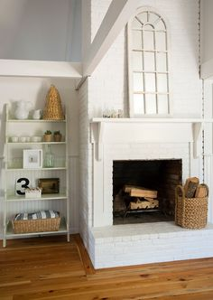 This fireplace is in the dining room. It originally had a dark and ugly combination of different colored bricks; McGuill brought out the white paint and added a very simple and inexpensive mantel.