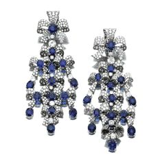 PAIR OF SAPPHIRE AND DIAMOND PENDENT EAR CLIPS, MICHELE DELLA VALLE. Each designed as a stylised cascade of tied knots, set with oval sapphires, brilliant- and circular-cut diamonds, signed Michele della Valle and numbered, pochette.