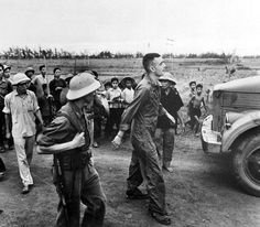 """Captured American Pilot. Capt. Charles Boyd, U.S. Air Force, is escorted by his captors to a """"prisoners' gathering point."""" His aircraft was down on a mission in April 1966."""