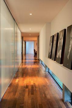 """""""O desenho de mão-francesa invertida desta parede de Drywall, projetada pelo arquiteto Marco Peres, forma uma espécie de prateleira. Com isso, os quadros ficam apoiados na parede, sem necessidade de furos. Repare que ele fez um rasgo de 15 cm de altura junto ao chão para a entrada de luz natural."""" (Foto: Edu Castello/Editora Globo)"""