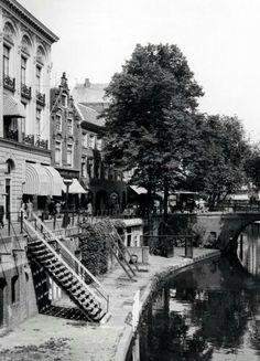 """""""De Oude Gracht"""" te Utrecht. Langs het water van de Oude Gracht de kaden met de werfkelders waar bedrijfjes in zijn gevestigd. Met een trap kan je vanaf de kade naar boven naar de straat waar het verkeer rijdt en statige huizen en winkelpanden staan. Utrecht, 1938"""
