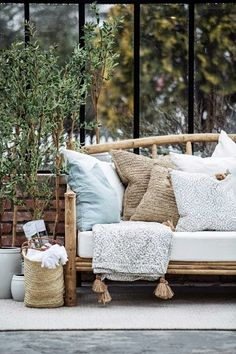 variety of neutral pillows. greenery. and multiple textures.