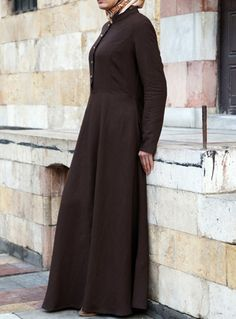 Ubayda Abaya Dark Chocolate color One of our favorite pieces and silhouettes for spring, the Ubayda Abaya is effortlessly chic and easy to wear. In addition to the flattering cut, the clean lines, beautiful buttons and practical pockets all work together for a unique and refined look. A great day-to night piece, this will surely be a wardrobe must-have.