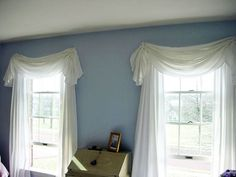 make a valance from an oval tablecloth, ribbon and cup hooks.