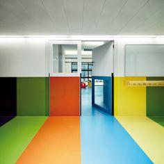 Nursery In The Jardines De Malaga In Barcelona / Batlle i Roig Arquitectes, colored hallway, daycare, door with alternating high low relite, hight door hardware, wood coat hooks