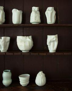 Handmade white ceramic vases against a dark wood dining room hutch
