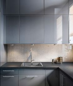 Kitchen with ABSTRAKT grey high-gloss doors/drawer fronts and PRÄGEL black stone effect worktop
