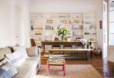 comedor de un piso con una gran mesa de madera y un banco estanteria blanca de fondo
