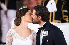 Adoring: Prince Carl Philip of Sweden, with his slicked back hair, smiles kisses his new wife Princess Sofia of Sweden