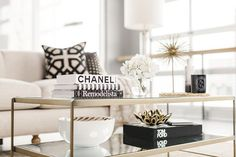 Living space with a sold and glass coffee table styled with fashion books and white hydrangeas