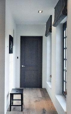 Black door, black windows, black shades, white walls & ceiling, no baseboards or crown molding, wood floors.