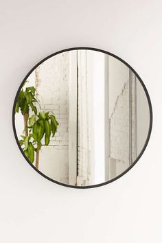 """Umbra Oversized Hub Mirror - Oversized glass mirror with a black rubber trim designed by Paul Rowan. We love this piece to make smaller living spaces appear larger. Statement piece on its own in any room. Depth: 2"""" and Diameter: 36"""""""