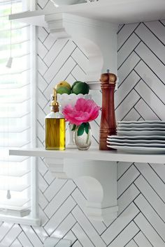 Open shelves sit on top of a herringbone backsplash accented with charcoal grout.