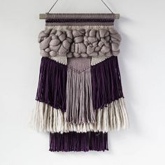 Add a pop to any wall with this fluffy purple woven wall hanging! This piece is one of a kind and was made with cotton, 100% wool yarns, and merino roving. Hanging from a wooden dowel it measures approximately 11.5 in. wide and 18 in. long. The dowel measures 11 in long. Love what