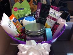 Spa tub b-day gift Lotion, nail polish, polish remover, cuticle set, facial scrub, candle, fuzzy socks, eye mask, lip balm, and face moisturizer.