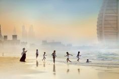 Mother's Prayer on Jumeirah Beach    A backdrop of the 7 star Burj Al Arab in Dubai and a mother offering her prayers while her children make merry. Photograph by © Enjo Mathew. A very WONDERFUL and touching moment!!
