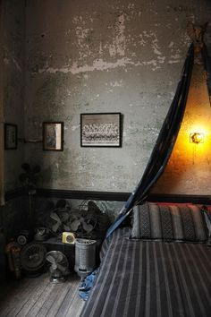 Masculine bedroom with antique industrial objects. by catalina - I like the drape over the bed, but I'd do it in filmy white fabric.