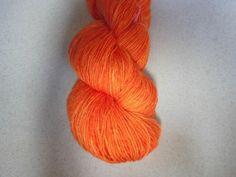 Varm frisk orange håndfarvet strømpegarn med diskret glitter.  Garn i en tynd kvalitet, en  populær garntykkelse til mange strikkeprojekter.…