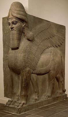 An ancient Assyrian gypsum alabaster lamassu (a human-headed winged lion), whose 'horned cap attests to their divinity, and belt signifies their power', generally, symbols of protection and support. (Metropolitan Museum of Art)